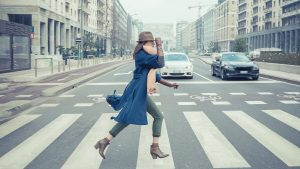 Frau mit Hut und Schal schützt sich vor Autoabgasen in der Stadt
